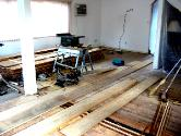 wide pine planks stacked up and being installed